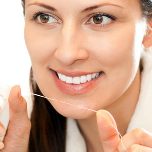 Smiling woman holding floss