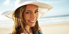 Young woman on beach with flawless smile