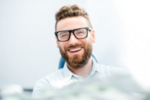 red head man in glasses smiling